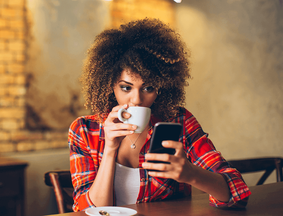 lady look at her phone app while drinking coffee