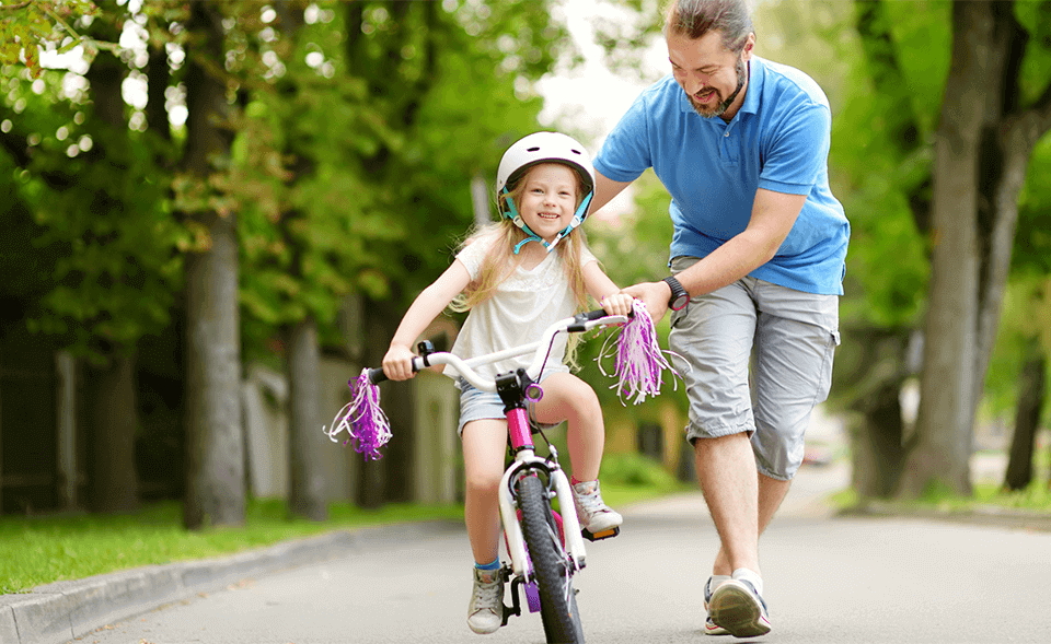 dad teaching daughter to ride her first bike