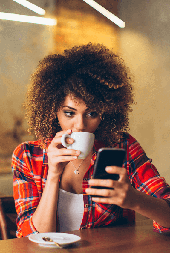woman in a red plaid shirt drinking coffee and looking at her mobile banking app on her cell phone